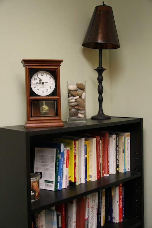 Caroline Madden's book shelf also the therapy hour clock
