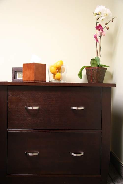 therapy office file cabinet with clock, tissue holder, lone and an orchid