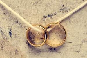 two wedding rings with ribbon thread through them